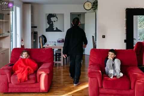 Un garçon et une fille sont assis dans des chaises séparées en regardant la télévision sur cette image capturée par un photojournaliste de la famille de l'Hérault.
