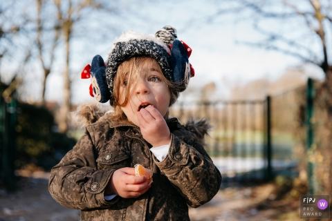 Un petit garçon mange une orange à l'extérieur sur cette photo réalisée par un photojournaliste de la famille héraultaise.