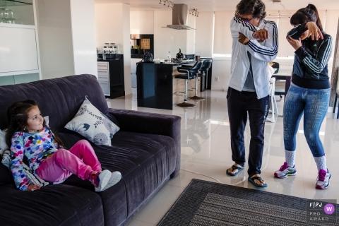 Une mère et un père prétendent avoir une trompe d'éléphant que leur fille regarde dans cette photo récompensée par une photojournaliste familiale primée par un photographe de famille documentaire de Rio Grande do Sul, Brésil.