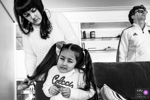 Une fille grimace lorsque sa mère met ses cheveux en nattes dans cette image primée du FPJA, capturée par un photographe de famille du Rio Grande do Sul, au Brésil.