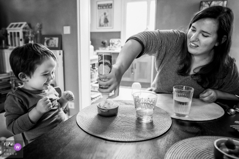 A little boy excitedly watches as his mother puts whipped cream on his dessert in this photograph created by a France family photojournalist.