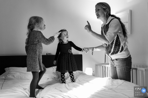 A mother scolds her two daughters for jumping on the bed in this FPJA award-winning picture by a Gelderland, Netherlands family photographer.