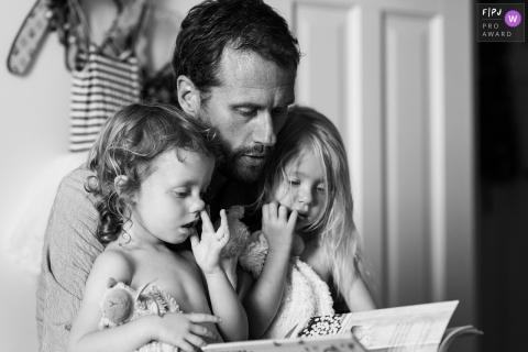 Un père lit un livre à ses deux enfants dans cette photo de famille de style documentaire prise par un photographe des Pays-Bas, dans la Gueldre.