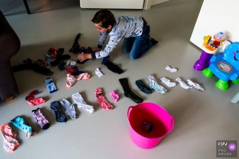 Un garçon travaille sur des chaussettes pliantes dans cette image primée du FPJA, capturée par un photographe de la famille Modena.