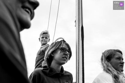 A family enjoys some time on their sailboat in this image created by an Eindhoven family photographer.