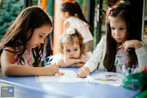 Deux filles se colorent pendant que leur sœur cadette regarde cette photo prise par un photojournaliste de la famille arménienne.