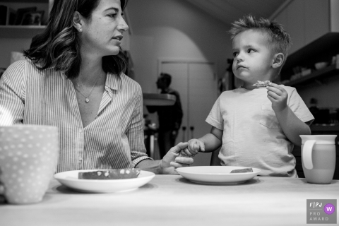 A son looks questioningly at his mother as he eats his breakfast in this documentary-style family image recorded by a Boulder, CO photographer.