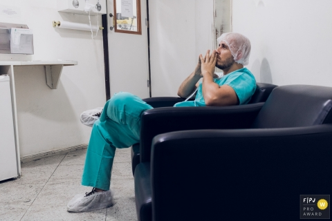 A father waits anxiously in the hospital as his wife gives birth in this photo captured by a Rio de Janeiro, Brazil documentary birth photographer.