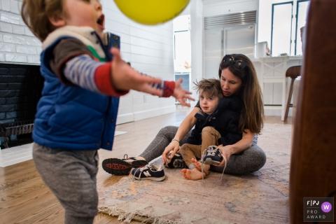 Une mère aide son fils à mettre ses chaussures alors que son frère joue au ballon sur cette photo réalisée par un photographe de famille documentaire de Los Angeles, Californie.