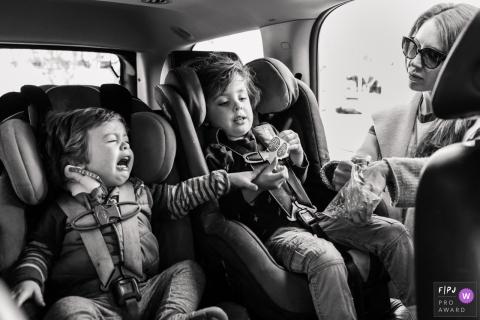 Une mère prend une collation pour ses fils assis dans leurs sièges d'auto dans cette photo récompensée par la photo photo par un photographe de famille documentaire de Los Angeles, Californie.