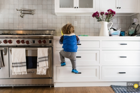 A little boy climbs kitchen drawers to reach the counter in this FPJA award-winning image captured by a Los Angeles, CA family photographer.