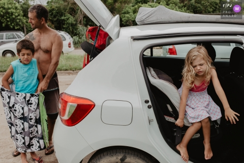 An unhappy girl gets out of the car to join her brother and father in this photo recorded by a Florianopolis award-winning, documentary-style family photographer.