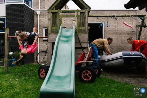 Two girls play on a swing set as their father and brother move an inflatable boat in this FPJA award-winning picture by a Netherlands family photographer.