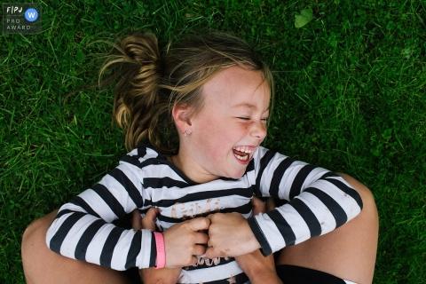 Une petite fille gît dans l'herbe en riant sous le regard de quelqu'un qui la chatouille dans cette photo de famille au style documentaire prise par un photographe néerlandais.