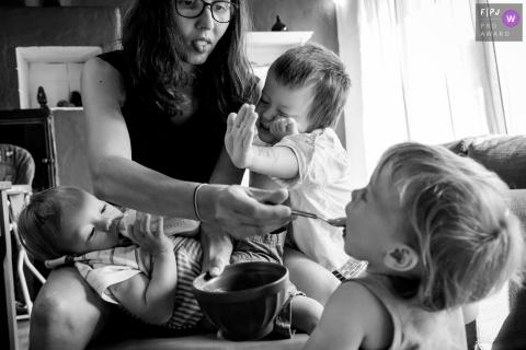 Une mère tente de nourrir ses trois jeunes enfants simultanément sur cette photo réalisée par un photographe de famille documentaire de Nantes.