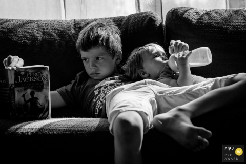 A boy reads on the couch while his little brother drinks his bottle next to him in this FPJA award-winning image captured by a Nantes family photographer.