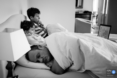 Two boys sit in bed while their father sleeps next to them in this award-winning photo by a Nantes family photographer.