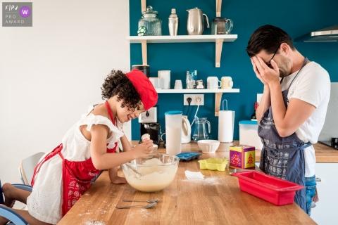 Un père couvre ses yeux alors que sa fille ajoute un ingrédient à leur pâte à biscuits dans cette image capturée par un photojournaliste de la famille nantaise.