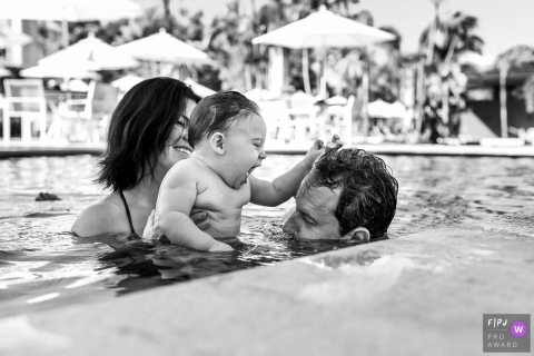 A baby plays with his mother and father in a pool in this Family Photojournalist Association contest awarded photo created by a Sao Paulo, Brazil family photographer.