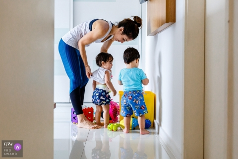A mother helps her child get dressed in this FPJA award-winning picture by a Sao Paulo, Brazil family photographer.