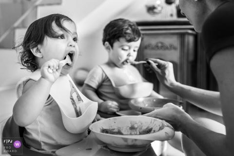 Une petite fille mange son déjeuner pendant que sa mère nourrit son frère dans cette photo de famille au style documentaire prise par un photographe de Sao Paulo, Brésil.