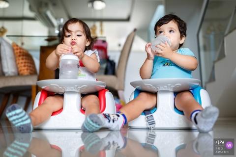 Un garçon et une fille mangent et boivent sur leur chaise par terre dans cette photo de famille réalisée par un photographe de Sao Paulo, Brésil.