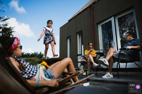 Une fille se promène sur une table alors que sa famille est assise à l'extérieur dans cette photo récompensée par une photo d'un photographe de famille documentaire d'Amsterdam.