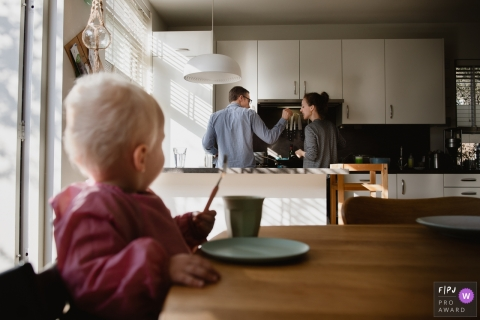 A husband has his wife taste what he is cooking as their baby sits at the kitchen table watching in this FPJA award-winning image captured by an Amsterdam family photographer.