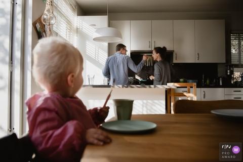 Un mari demande à sa femme de goûter à ce qu'il fait cuire pendant que leur bébé est assis à la table de la cuisine et regarde cette image primée du FPJA, capturée par un photographe de la famille d'Amsterdam.