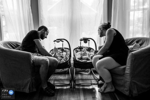 A mother and father watch their two babies in the living room in this photo by a Boston, MA award-winning family photographer.