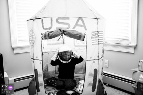 A little boy plays inside a large, play rocket ship in this photograph created by a Boston, MA family photojournalist.