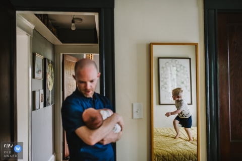 Un père tient son bébé alors que son fils saute sur le lit dans un miroir dans cette photo de famille au style documentaire prise par un photographe de Boston, Massachusetts.