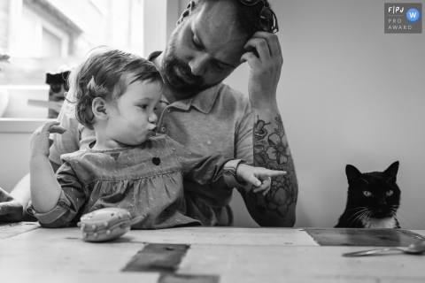 A father looks at his daughter as she points at a cat in this photo recorded by a Netherlands award-winning, documentary-style family photographer.