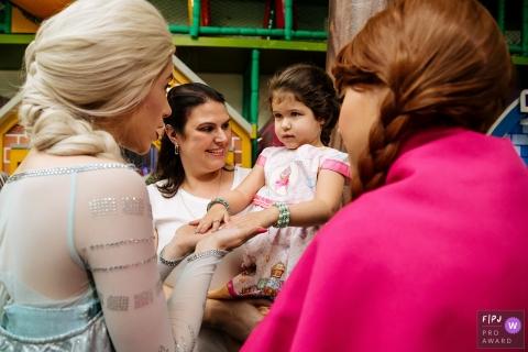 Une mère tient sa fille dans ses bras lorsqu'elle rencontre Elsa et Anna de Frozen sur cette photo prise par un photojournaliste de la famille de Sao Paulo.