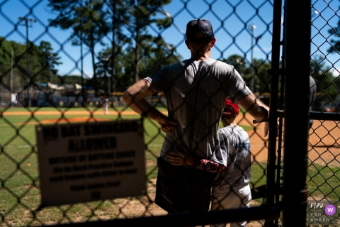 A son puts his arm around his father on the sidelines during a baseball game in this photo by an Atlanta, GA award-winning family photographer.