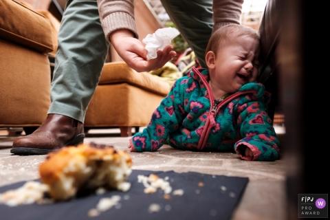 Un père réconforte sa fille en pleurs qui repose à côté d'un petit gâteau tombé par terre sur cette photo réalisée par un photojournaliste de la famille d'Atlanta, en Géorgie.