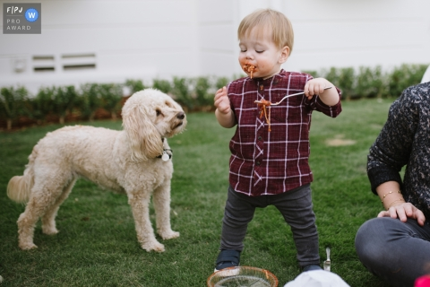 Un petit garçon mange des spaghettis à l'extérieur pendant que son chien l'observe dans cette image familiale de style documentaire enregistrée par un photographe de Los Angeles, en Californie.