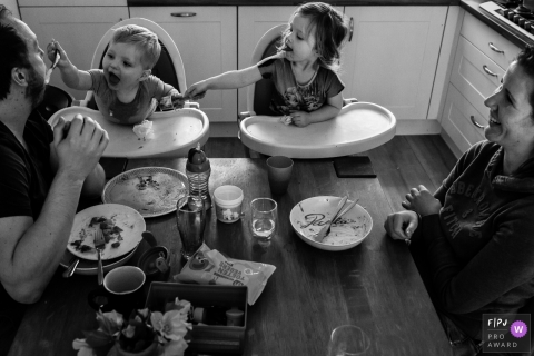 A little boy tries to feed his father in a surprising role reversal in this Family Photojournalist Association contest awarded photo created by a Netherlands family photographer.