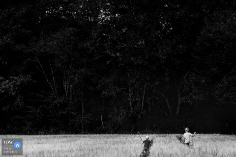 Two boys walk through tall grass as one carries a toy sword in this family picture by a Copenhagen, Denmark photographer.