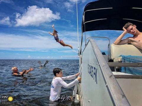 Une famille apprécie une journée sur un bateau alors qu'une petite fille saute à l'eau dans cette photo primée par la Family Photojournalist Association par un photographe de famille documentaire de Key West, en Floride.