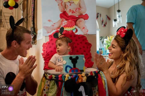 A mother and father celebrate their daughter's first birthday with a Mickey Mouse cake in this FPJA award-winning image captured by a Florida family photographer.