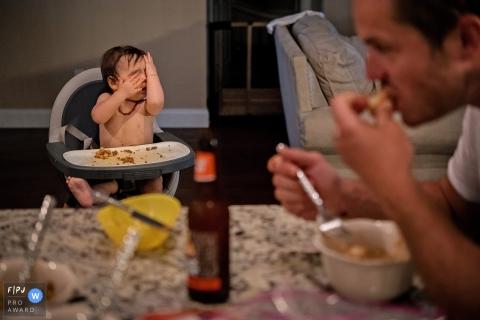 Un petit garçon est assis dans sa chaise haute pour le déjeuner et couvre son visage de ses mains sur cette photo enregistrée par un photographe de famille de style documentaire primé à Key West, en Floride.