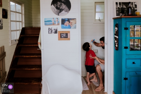 A father brushes his son's teeth in this photo by a Florianopolis award-winning family photographer.