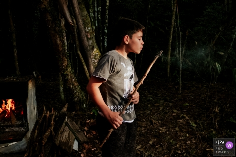 A boy blows out a flame on the end of a stick during a camping trip at night in this photograph created by a Florianopolis family photojournalist.