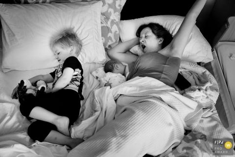 Une mère endormie allaite son bébé au lit tandis que son fils est allongé à côté d'elle dans cette photo de famille au style documentaire prise par un photographe de Key West, en Floride.