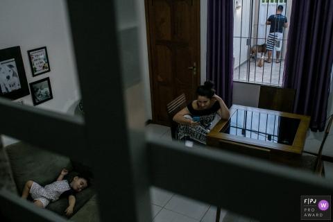 Une mère est assise à une table pendant que son fils dort sur le canapé sur cette photo réalisée par un photographe de famille documentaire de Rio de Janeiro.
