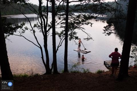 Un homme se tient sur un radeau pendant que son fils se tient dans l'eau pendant que sa mère observe cette image créée par un photographe de famille à Saint-Pétersbourg, en Russie.