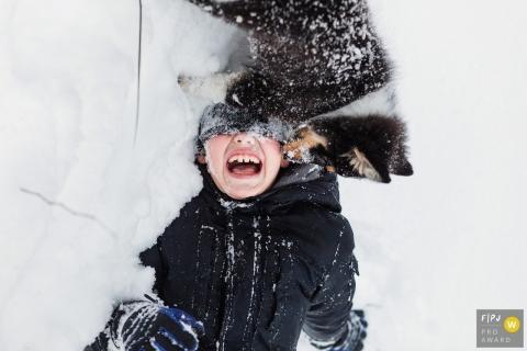 Un garçon joue dans la neige avec son chiot sur cette photo enregistrée par un photographe de famille de style documentaire primé à Saint-Pétersbourg, en Russie.