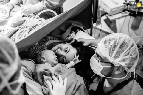 A mother meets her infant for the first time in the hospital as the doctor closes her C-section in this photo by an award-winning Minas Gerais birth photographer.