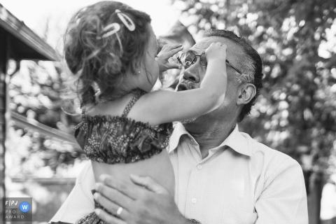 Une petite fille essaie d'enlever les lunettes de son grand-père sur cette photographie créée par un photojournaliste de la famille de Seattle, WA.